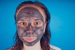 女孩投入了粉刺的面罩 脸面护理的概念 免版税库存图片