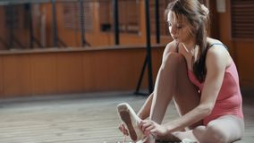 女孩投入在她的芭蕾舞鞋的balerina舞蹈家 图库摄影