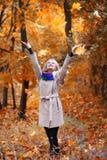 女孩投掷叶子在秋天公园 库存照片