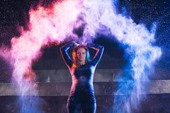 女孩投掷和舞蹈与颜色粉末在黑暗的背景 库存图片