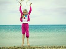 女孩投掷在海滩的几壳 免版税库存图片