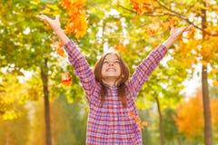 女孩投掷槭树桔子在秋天公园离开  免版税库存图片