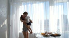 女孩投掷男孩并且拥抱他 妈妈对她的儿子满意 股票视频