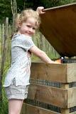 女孩投掷的垃圾到容器里 免版税库存图片