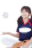 女孩投掷的垒球在航空,当坐时 库存照片