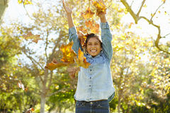 女孩投掷的秋叶在天空中 免版税图库摄影