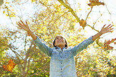 女孩投掷的秋叶在天空中 库存照片