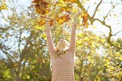 女孩投掷的秋叶在天空中 免版税库存照片
