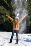 女孩投掷的雪在天空中 免版税库存图片