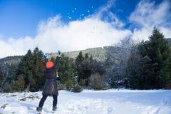 女孩投掷的雪球的行动片刻在天空中与她的面对照相机的后面 库存图片