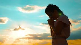 女孩折叠了她的在祷告剪影的手在日落 慢动作录影 女孩折叠了她的在祷告的手祈祷给上帝 股票录像