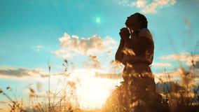 女孩折叠了她的在祷告剪影的手在日落 祈祷在她的膝盖的妇女 慢动作录影 女孩折叠了她 影视素材