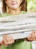 女孩报纸回收 免版税图库摄影