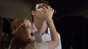 女孩抹上婚宴喜饼片断在新郎的面孔的 婚姻庆祝的玻璃 股票录像