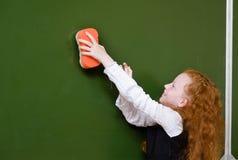 女孩抹黑板与海绵 免版税库存图片