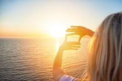 女孩拉扯她的手对在海的背景的太阳 她看太阳通过她的拇指 免版税库存图片