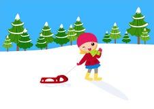 女孩拉扯雪撬 免版税库存照片