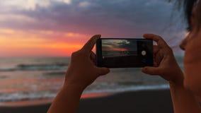 女孩拍在智能手机的照片,在海的黎明 免版税库存照片
