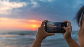 女孩拍在智能手机的照片 免版税库存照片