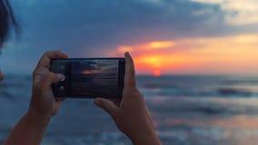 女孩拍在智能手机的照片 库存图片