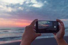 女孩拍在智能手机黎明的照片在海 库存照片