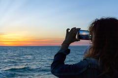 女孩拍摄了与智能手机的日落 图库摄影