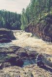 女孩拍摄峭壁和动荡河,芬兰 免版税库存图片
