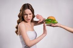女孩拒绝吃被隔绝的大汉堡 免版税图库摄影