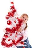 女孩拥抱一个白色圣诞节结构树 图库摄影