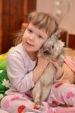 女孩拥抱一只兔子 免版税库存图片