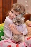 女孩拥抱一只兔子 免版税图库摄影
