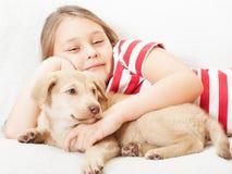 女孩拥抱一只小狗 免版税库存图片