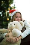 女孩拥抱在圣诞前夕的玩具熊 免版税图库摄影