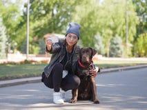 女孩拥抱她的狗,当蹲狗时 免版税图库摄影
