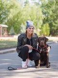 女孩拥抱她的狗,当蹲狗时 免版税库存照片