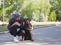 女孩拥抱她的狗,当蹲狗时 库存照片