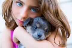 女孩拥抱小的小狗灰色长毛的奇瓦瓦狗 免版税库存图片