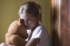 女孩拥抱玩具熊在家 免版税图库摄影