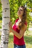 女孩拥抱的桦树 库存图片