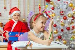 女孩拾起在头的玩具烟花,坐在她后的圣诞老人 免版税库存照片