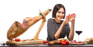 女孩拿着一个三明治用肉和逗人喜爱的微笑 查出在空白背景 免版税库存图片