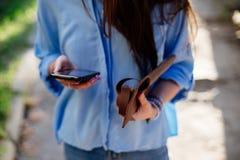 女孩拿着一个女用无带提包和电话 免版税库存图片