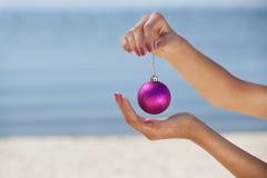 女孩拿着一个桃红色圣诞节球,背景被看见海 免版税库存图片