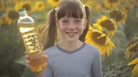 女孩拿着一个瓶菜油和立场在领域用向日葵 农业,有机和健康食品 股票视频
