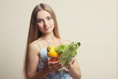 女孩拿着一个碗新鲜蔬菜 免版税库存照片