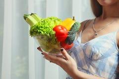 女孩拿着一个碗新鲜蔬菜 库存图片