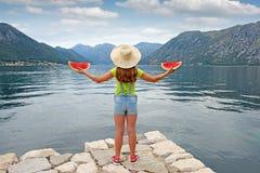 女孩拿着一个西瓜并且在海科托尔海湾附近站立 免版税库存照片