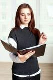 女孩拿着一个黑文件夹开放在一只手上和在其他上她 免版税图库摄影