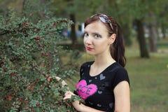 女孩拿着一个dogrose分支用红色莓果 免版税库存图片