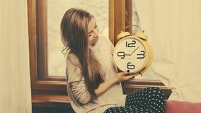 女孩拿着一块手表 库存图片